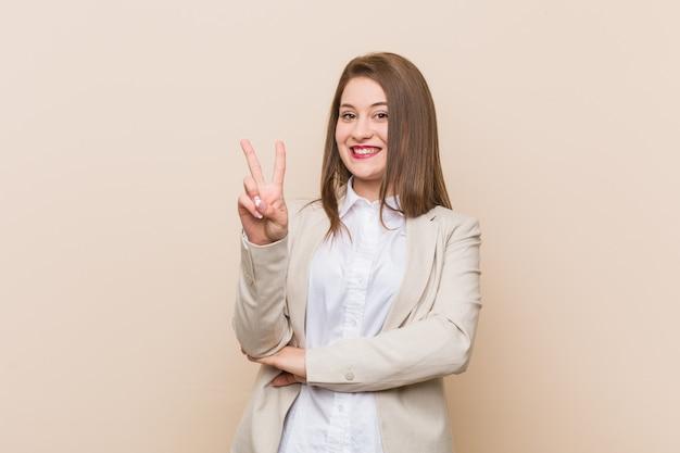 Mulher de negócios jovem mostrando o número dois com os dedos.