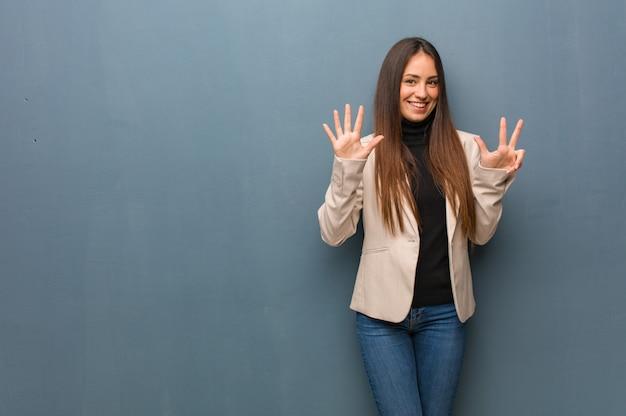 Mulher de negócios jovem mostrando o número oito