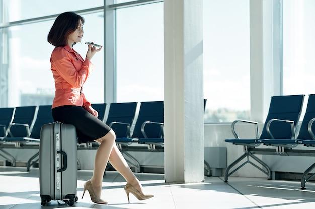 Mulher de negócios jovem no aeroporto com bagagem, grava uma mensagem de áudio no telefone e sorrindo.