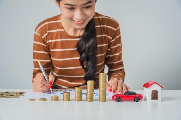 Mulher de negócios jovem olhando a pilha de moedas, analisando o gráfico de finanças