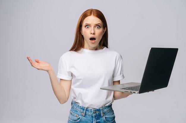 Mulher de negócios jovem ou estudante chocada com a boca aberta segurando o computador laptop aberto