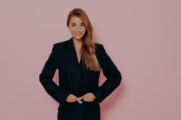 Mulher de negócios jovem positiva mantendo as mãos nos bolsos de um terno formal preto, satisfeita com o dia de trabalho, posando com um sorriso magnífico no rosto contra um fundo rosa, demonstrando confiança