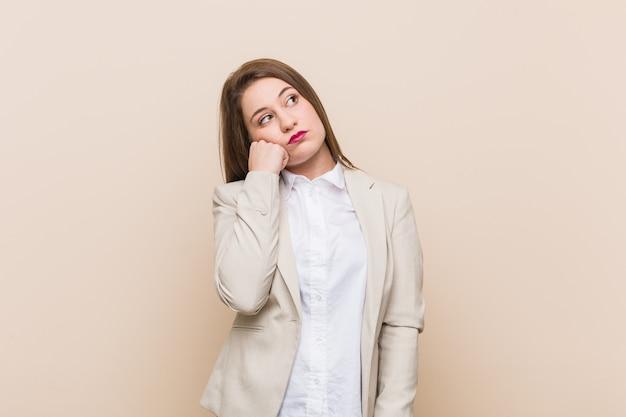 Mulher de negócios jovem que se sente triste e pensativa, olhando para a cópia.