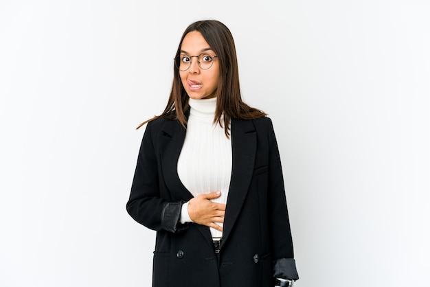 Mulher de negócios jovem raça mista isolada no fundo branco toca a barriga, sorri suavemente, comendo e conceito de satisfação.
