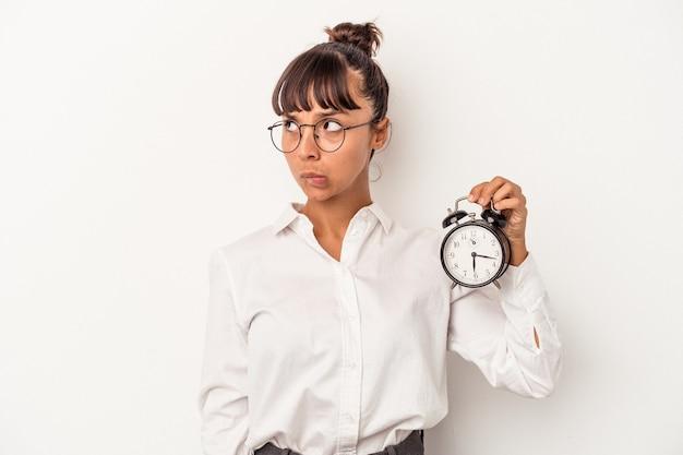 Mulher de negócios jovem raça mista segurando um despertador isolado no fundo branco confusa, sente-se duvidosa e insegura.