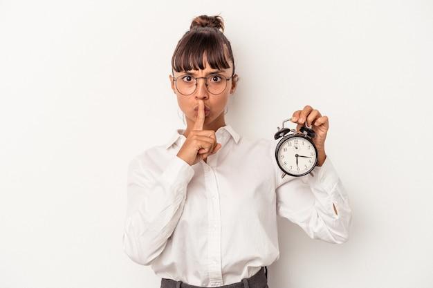 Mulher de negócios jovem raça mista segurando um despertador isolado no fundo branco, mantendo um segredo ou pedindo silêncio.