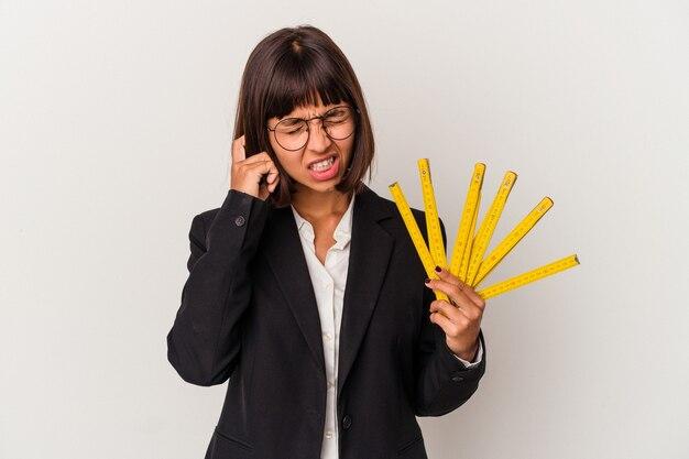 Mulher de negócios jovem raça mista segurando uma fita métrica isolada no fundo branco, cobrindo as orelhas com as mãos.