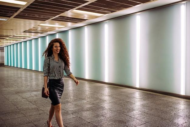 Mulher de negócios jovem ruiva caminhando para o trabalho