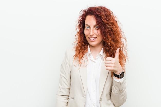 Mulher de negócios jovem ruiva natural isolada contra branco sorrindo e levantando o polegar para cima
