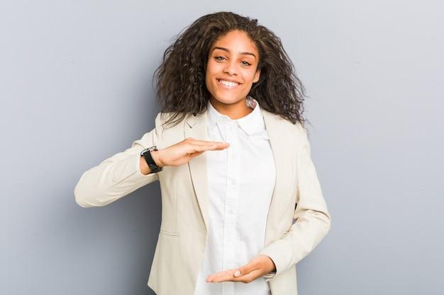 Mulher de negócios jovem segurando algo com ambas as mãos, apresentação do produto
