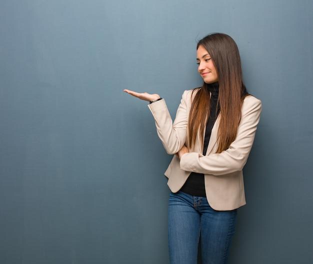Mulher de negócios jovem segurando algo na palma da mão