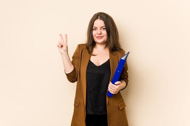 Mulher de negócios jovem segurando arquivos mostrando o número dois com os dedos.