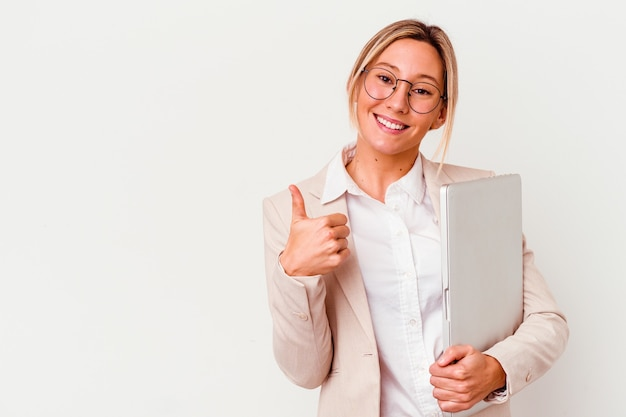 Mulher de negócios jovem segurando um laptop isolado na parede branca, sorrindo e levantando o polegar