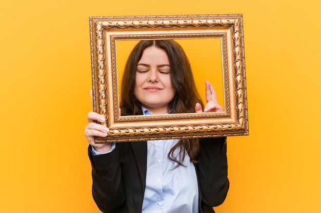 Mulher de negócios jovem segurando um quadro cruzando os dedos por ter sorte