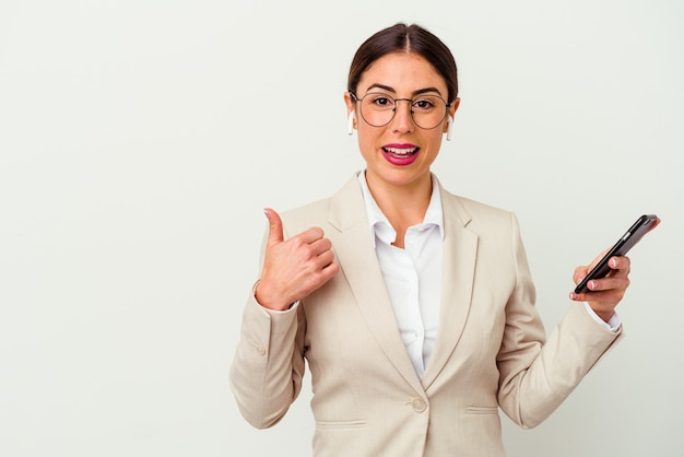 Mulher de negócios jovem segurando um telefone celular isolado no fundo branco, sorrindo e levantando o polegar