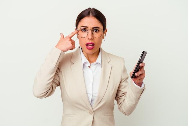 Mulher de negócios jovem segurando um telefone móvel isolado no fundo branco, mostrando um gesto de decepção com o dedo indicador.