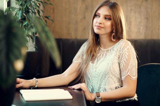 Mulher de negócios jovem sentado à mesa em uma cafeteria e fazendo anotações