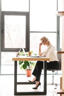 Mulher de negócios jovem séria usando o laptop, olhando de lado.