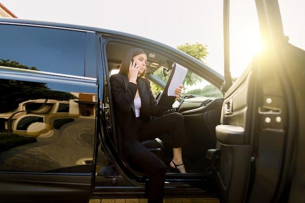 Mulher de negócios jovem sério vestida com roupa formal, conversando com o parceiro via telefone celular e usando a área de transferência enquanto está sentado no automóvel de luxo preto