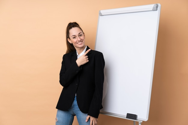 Mulher de negócios jovem sobre parede isolada, dando uma apresentação no quadro branco e apontando para o lado
