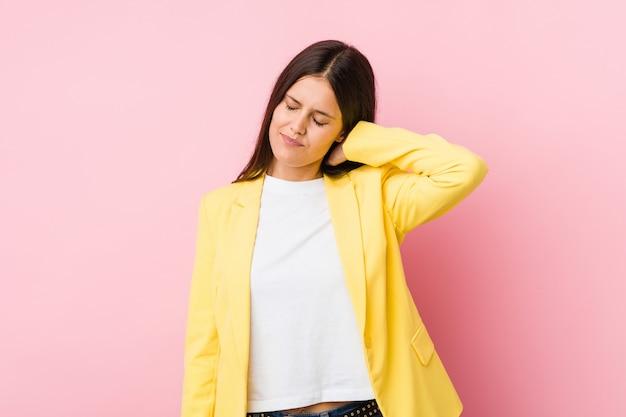 Mulher de negócios jovem sofrendo dores no pescoço devido ao estilo de vida sedentário.
