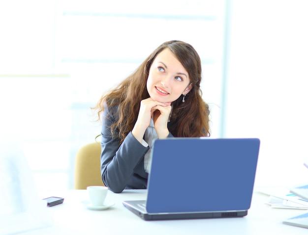 Mulher de negócios jovem sonhadora, trabalhando com o laptop.
