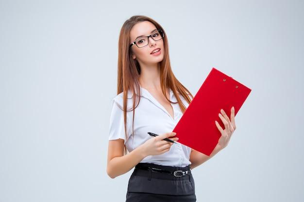 Mulher de negócios jovem sorridente de óculos com caneta e tablet para anotações em um fundo cinza