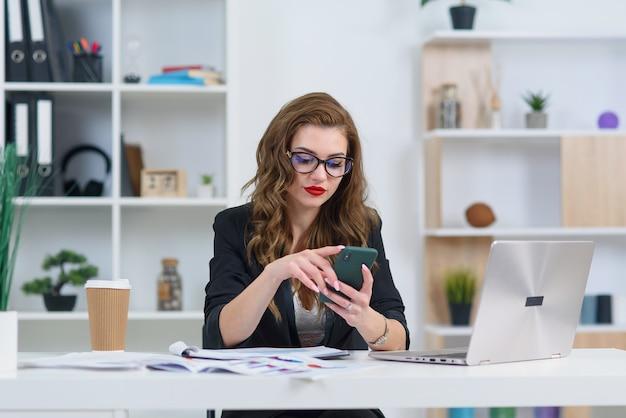 Mulher de negócios jovem sorridente em roupas elegantes, sentado no escritório moderno acolhedor e procurar algo no smartphone.