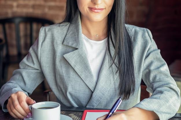 Mulher de negócios jovem sorridente está escrevendo para notebook, bebendo café no café. conceito de negócio ou trabalho.