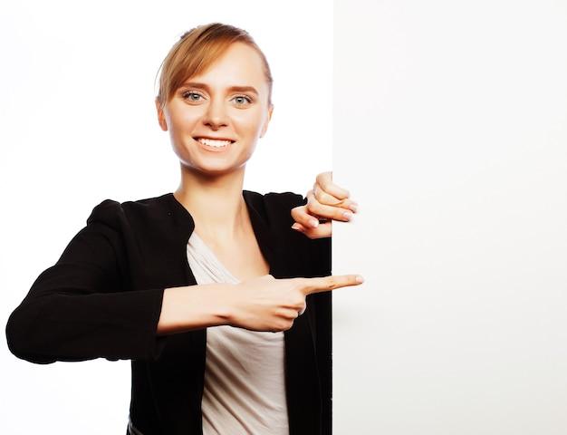 Mulher de negócios jovem sorridente feliz mostrando uma tabuleta em branco sobre fundo branco