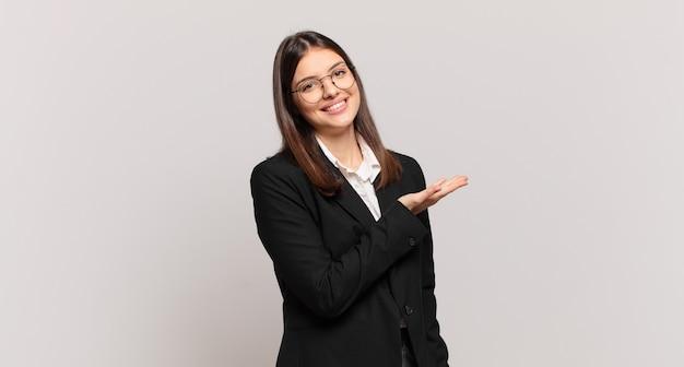 Mulher de negócios jovem sorrindo alegremente, sentindo-se feliz e mostrando um conceito no espaço da cópia com a palma da mão