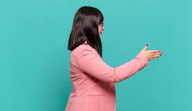 Mulher de negócios jovem sorrindo, cumprimentando você e oferecendo um aperto de mão para fechar um negócio de sucesso, o conceito de cooperação
