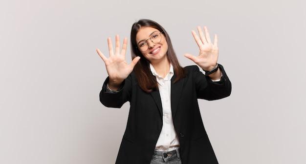 Mulher de negócios jovem sorrindo e parecendo amigável, mostrando o número dez ou décimo com a mão para a frente, em contagem regressiva