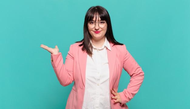 Mulher de negócios jovem sorrindo, sentindo-se confiante, bem-sucedida e feliz, mostrando o conceito ou ideia no espaço da cópia ao lado