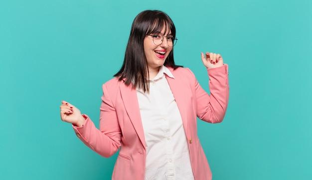 Mulher de negócios jovem sorrindo, sentindo-se despreocupada, relaxada e feliz, dançando e ouvindo música, se divertindo em uma festa