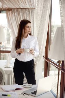 Mulher de negócios jovem tem uma pausa para café no seu local de trabalho