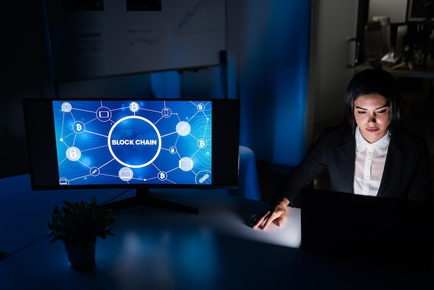 Mulher de negócios jovem trabalhando à noite dentro do escritório da empresa fintech, fazendo pesquisa de blockchain - comércio, investimento e conceito financeiro - foco no rosto