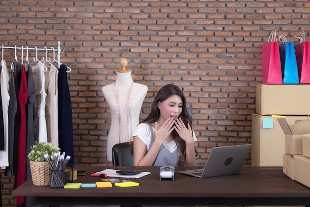 Mulher de negócios jovem trabalhando com vendas online. rosto de surpresa e choque do sucesso da mulher asiática em fazer uma grande venda de sua loja online. compras online