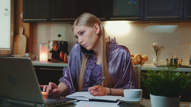 Mulher de negócios jovem trabalhando em casa, sentado no computador e falando pelo smartphone