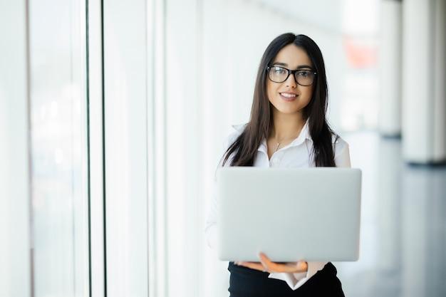 Mulher de negócios jovem trabalhando em seu luxuoso escritório segurando um laptop encostado em uma janela panorâmica com vista para o distrito comercial