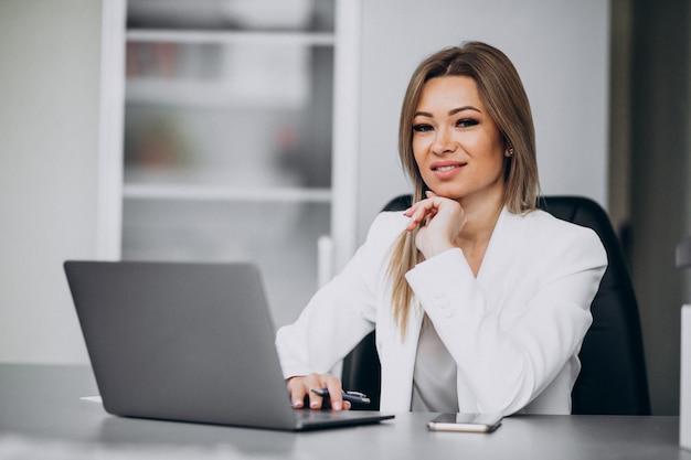 Mulher de negócios jovem trabalhando no laptop em um escritório