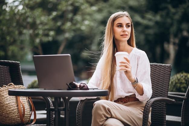 Mulher de negócios jovem trabalhando no laptop fora em um café