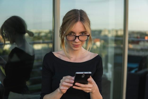 Mulher de negócios jovem usa telefone. mulher bonita usa banco on-line no telefone inteligente para transferir dinheiro do cartão de crédito. menina usando telefone inteligente e conversando com parceiros de negócios.