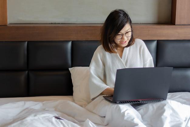 Mulher de negócios jovem usando o laptop na cama enquanto trabalha em casa