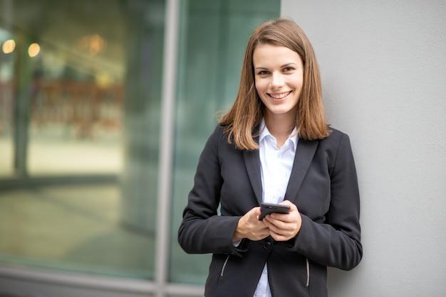 Mulher de negócios jovem usando seu telefone celular móvel