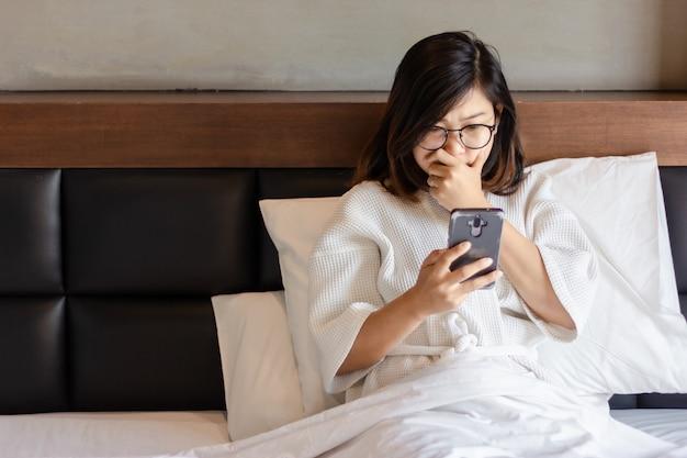 Mulher de negócios jovem usando smartphone na cama enquanto trabalha em casa