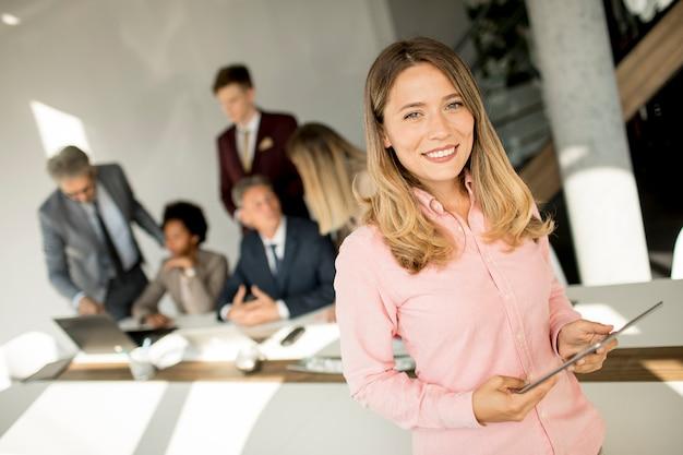 Mulher de negócios jovem usando tablet digital no escritório