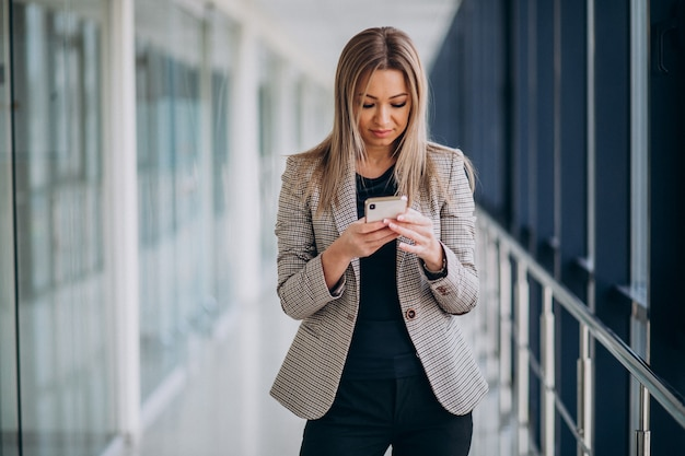 Mulher de negócios jovem usando telefone no terminal