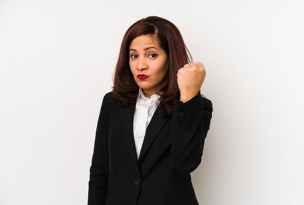 Mulher de negócios latina de meia idade isolada mostrando o punho para a frente, expressão facial agressiva
