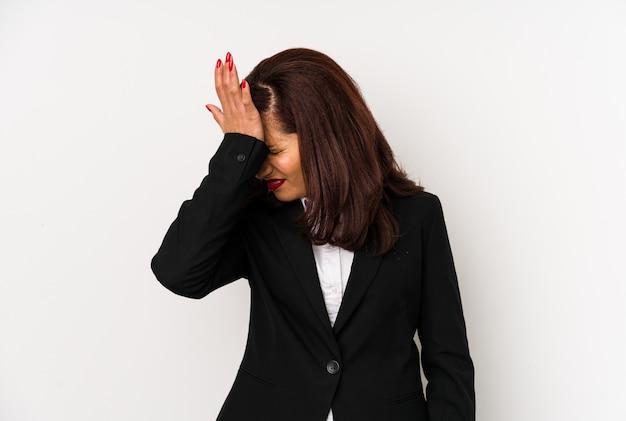 Mulher de negócios latino de meia-idade isolada esquecendo algo, batendo na testa com a palma da mão e fechar os olhos.